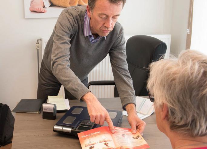 Diëtist geeft folder aan patiënte