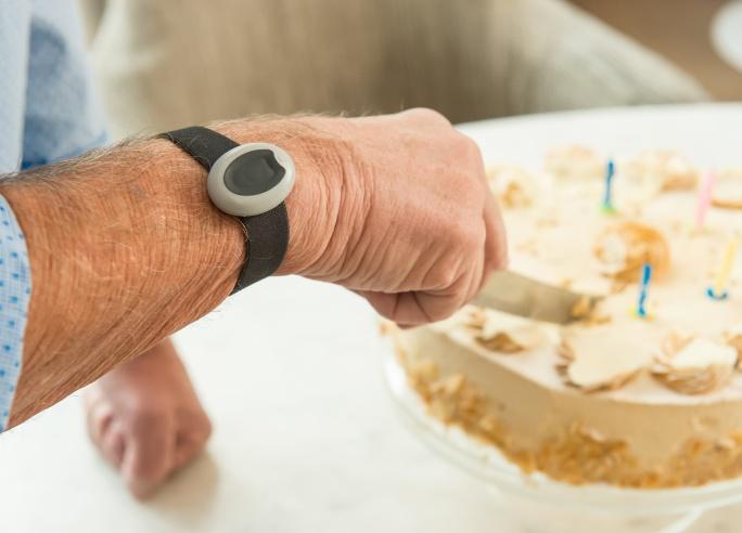 Personenalarm aan pols van persoon die taart snijdt