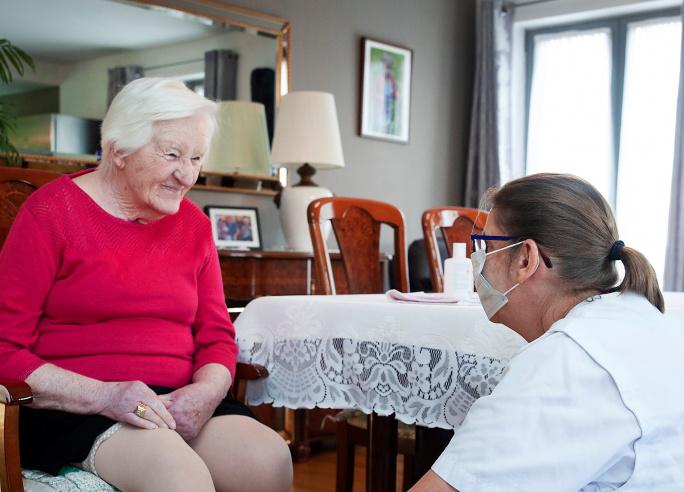 Verpleegkundige met mondmasker verzorgt patiënt